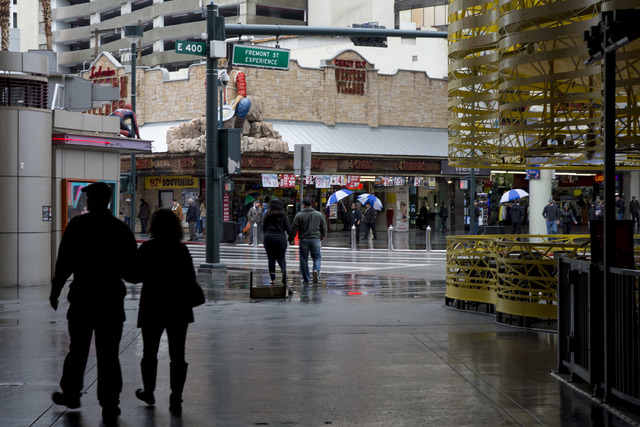 Puddles fill the street near the Fremont Street Experience as pedestrians walk under covered walk ways or with umbrellas on Saturday, Feb. 18, 2017, in downtown Las Vegas. On Friday a flash-flood  ...