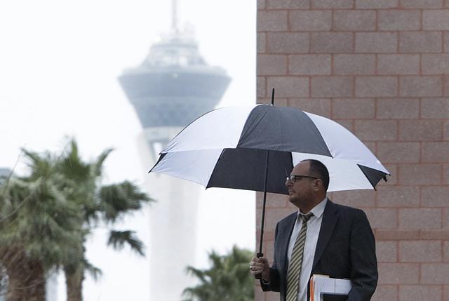 A pedestrian walks in the rain along Lewis Avenue near the Regional Justice Center on Friday, Jan. 20, 2017, in Las Vegas. (Bizuayehu Tesfaye/Las Vegas Review-Journal) @bizutesfaye
