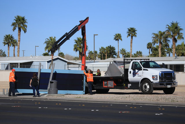 A crane is used to help move a fallen bus stop structure after a car hit and injured one person at the intersection of Sahara Avenue and Sandhill Road Friday, Feb. 24, 2017, in Las Vegas. (Brett L ...
