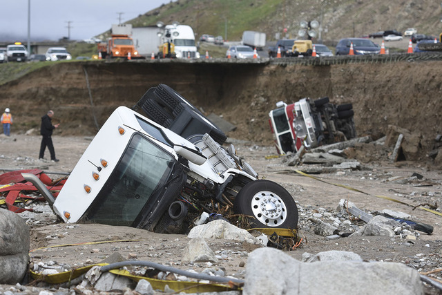 Officials look over the scene, Saturday, Feb. 18, 2017,  where  a tractor trailer fell Friday from southbound Interstate 15 where part of the freeway collapsed due to heavy rain in the Cajon Pass, ...