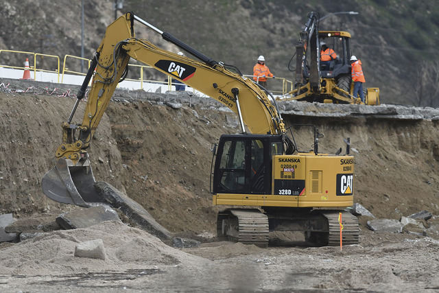 Workers with the California Department of Transportation repair a section of Interstate 15 on Sunday, Feb., 19, 2017, that washed away during a storm on Friday in the Cajon Pass., Calif. (David Pa ...