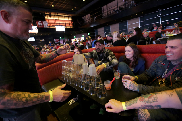 Will Fugate, from left, Ernesto Chaidez, Tylee Wood, and Swarm Wood stack empty drink cups while watching the Daytona 500 race on Sunday Feb. 26, 2017, at the showroom at the South Point hotel and ...