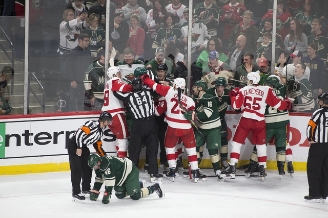 Minnesota Wild defenseman Jared Spurgeon (46) is attend to by referee Kyle Rehman (10) after being speared the face by Detroit Red Wings right wing Gustav Nyquist, of Sweden, (14) during the first ...
