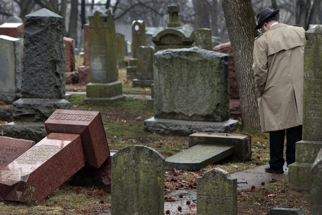 People walk through toppled graves at Chesed Shel Emeth Cemetery in University City, Mo., on Tuesday, Feb. 21, 2017. Authorities in Missouri are investigating after dozens of headstones were tippe ...