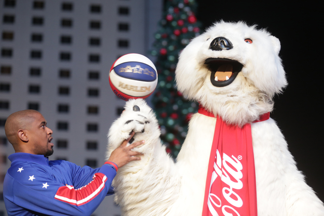 Scooter Christensen of the Harlem Globetrotters performs a trick with the Coca-Cola Bear on Monday, Nov. 21, 2016, at the tree lighting ceremony at The Park in Las Vegas. (Rachel Aston/Las Vegas R ...
