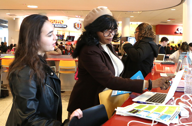 Cherie Hughes, right, navigator with Nevada Health Link, demonstrates how to login to Nevada Health Link website to UNLV student Yasmin Shahar during campus events for students to enroll in health ...