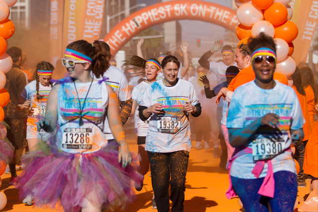 2015 Color Run participants run through the orange color station during the 5k Color Run course in downtown Las Vegas on Saturday, Feb. 28, 2015. (Donavon Lockett/Las Vegas Review-Journal)