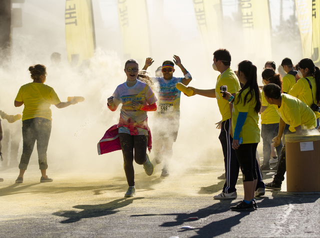 2015 Color Run participants run through the yellow color station during the 5k Color Run course in downtown Las Vegas, Nev., Saturday, Feb. 28, 2015. (Donavon Lockett/Las Vegas Review-Journal)