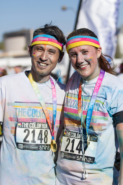2015 Color Run participants, husband and wife team, Ricky and Ashley Hernandez are all smiles as they pose for a picture after finishing the 5k Color Run course near Fremont street in downtown Las ...