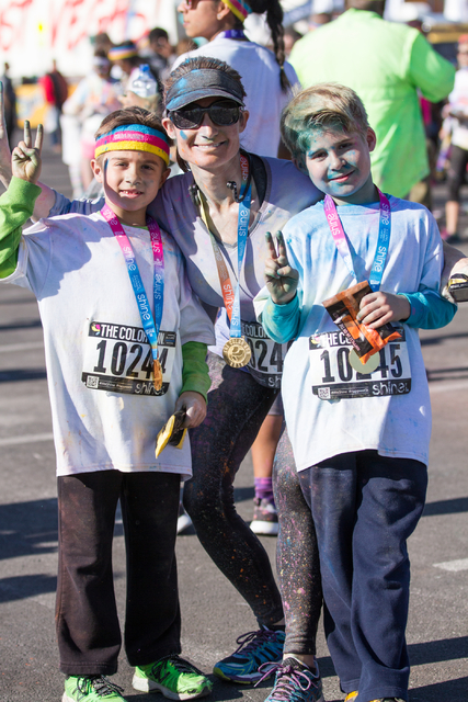2015 Color Run participants, from left, Zachary Hargett, his mom Robin Hargett, and twin brother Nathan Hargett pose for a picture after finishing the 5k Color Run course near Fremont Street in do ...