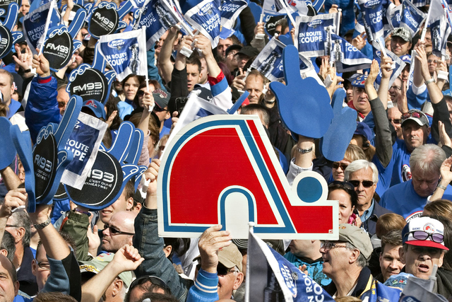 "Some of the tens of thousands of fans hold up signs and fingers during the ""Blue March,"" as fans asked for an NHL hockey team, 15 years after the Quebec Nordiques left town, Saturday, Oct. 2, 2010 ..."