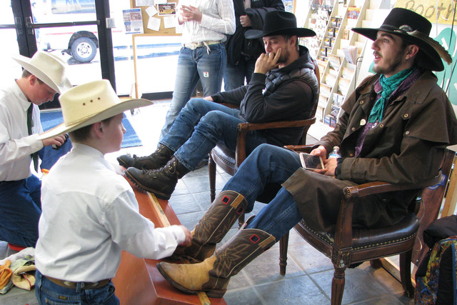Elko area youth Hardy Carlon shined Luke Rudolph's boots to help raise money for 4-H at the   National Cowboy Poetry Gathering at Elko Nev. on Feb. 3, 2017. Rudolph, a rancher from near Well, Ne ...