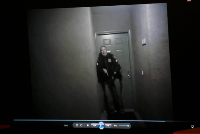 Footage from a body camera of officers attempting to evacuate residents taken during the officer-involved shooting that occurred on Feb. 25, 2015, in the 5300 block of East Craig Road, is played a ...