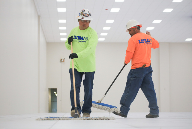 Jorge Sanchez, 41, center, and Marco Flores, 41, clean the floor of a server room expansion, built by Better Building Systems, at the ViaWest Lone Mountain Data Center on Friday, Feb. 24, 2017, in ...