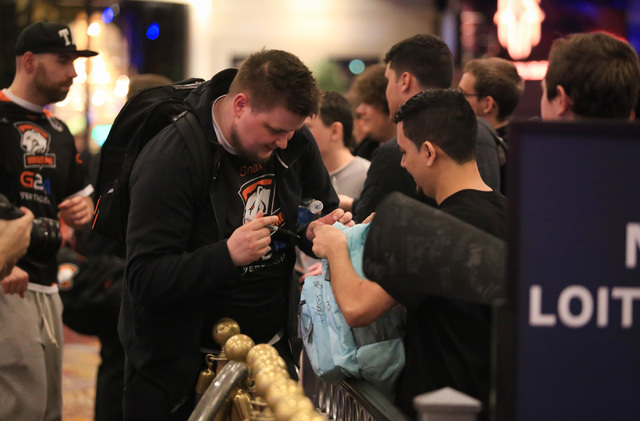 "Janusz ""Snax"" Pogorzelski, of Virtus.pro signs a fan's backpack after knocking Fnatic out of the group stage of DreamHack Masters Las Vegas at the MGM Grand hotel-casino in Las Vegas on Friday, Fe ..."