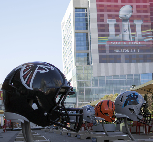 The Atlanta Falcons helmet (left), along with helmets from all 32 NFL teams, lines a plaza in front of the George R. Brown convention Center on Jan. 30, 2017, in Houston, Texas. (Heidi Fang/Las Ve ...