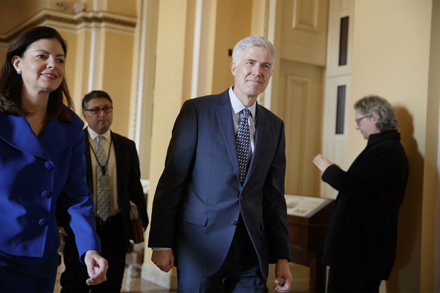 Supreme Court Justice nominee Neil Gorsuch is escorted by former New Hampshire Sen. Kelly Ayotte on Capitol Hill in Washington, Feb. 2, 2017. (J. Scott Applewhite/AP)