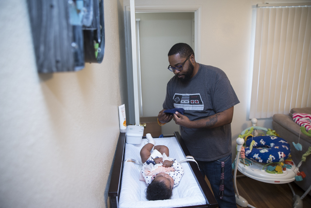 """Geoff """"Grant"""" Carlvin changes his 4-month-old daughter Penelope at their home on Wednesday, Jan. 25, 2017, in Las Vegas. Carlvin was diagnosed with multiple sclerosis three years ..."""