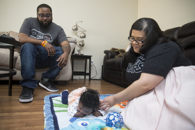 """Geoff """"Grant"""" Carlvin, left, with his wife Bridget and 4-month-old daughter Penelope at their home on Wednesday, Jan. 25, 2017, in Las Vegas. Carlvin was diagnosed with multiple  ..."""