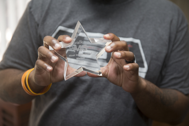 """Geoff """"Grant"""" Carlvin shows an award he received for being """"most inspirational walker"""" in a multiple sclerosis awareness walk, Wednesday, Jan. 25, 2017, in Las  ..."""