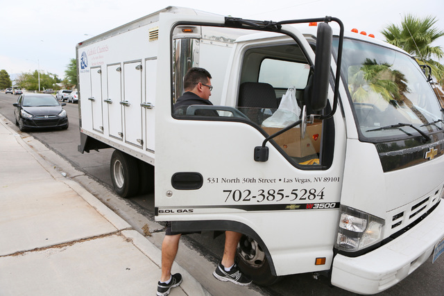 Catholic Charities of Southern Nevada Meals on Wheels Program driver Walter Johnson gathers groceries and dog food for a client outside the client's home Thursday, Aug. 5, 2016, in Las Vegas. (Ron ...