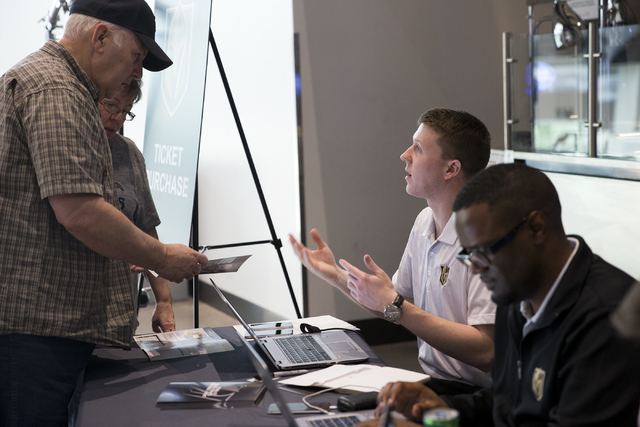 Jeff Ross, from left, with his wife Jeannine, receive assistance from Tom Heimrich, account executive for ticket services, during the Vegas Golden Knights 24-hour open house event at T-Mobile Aren ...