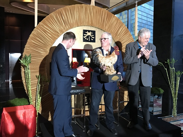 "Donald Bowman, general manager of the Mandarin Oriental Las Vegas, left, presents Golden Knights owner Bill Foley with a rooster nicknamed ""Stanley"" at Thursday's Chinese New Year celebration with ..."