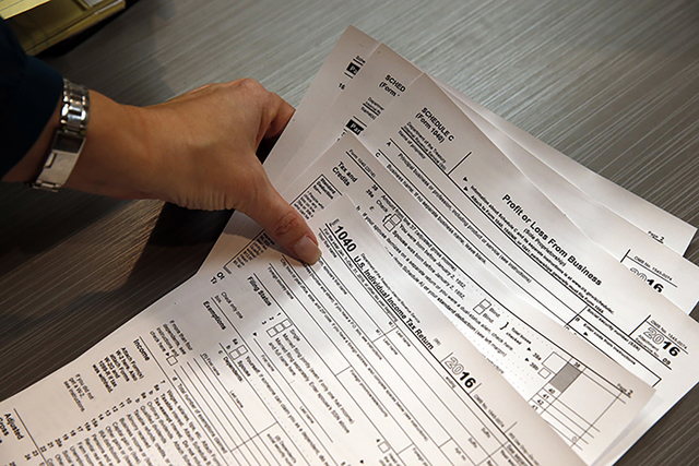 Tax professional and tax preparation firm owner Alicia Utley reaches for hard copies of tax forms while working to stay caught up at the start of the tax season, Jan. 14, 2017. (Brennan Linsley/AP)