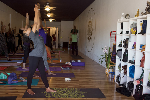 Carmella Gadsen, left, and other yogis participate in a two-day Kemetic yoga workshop. Some were regular Kemetic yoga practitioners, while others had little experience prior to the workshop. (Brid ...