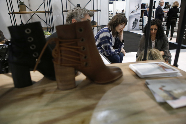 Nora Curtin, left, shops for shoes for her store as Heideh Fradi assists during the MAGIC fashion convention at the Las Vegas Convention Center on Tuesday, Feb. 21, 2017, in Las Vegas. Nora is the ...