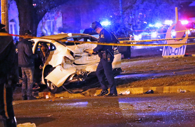 Police talk to a man sitting in a car that was struck by a pickup truck, that slammed into a crowd and other vehicles, causing multiple injuries, during the Krewe of Endymion parade in New Orleans ...