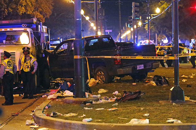 Police stand next to a pickup truck that slammed into a crowd and other vehicles, causing multiple injuries, coming to a stop against a dump truck, during the Krewe of Endymion parade in New Orlea ...