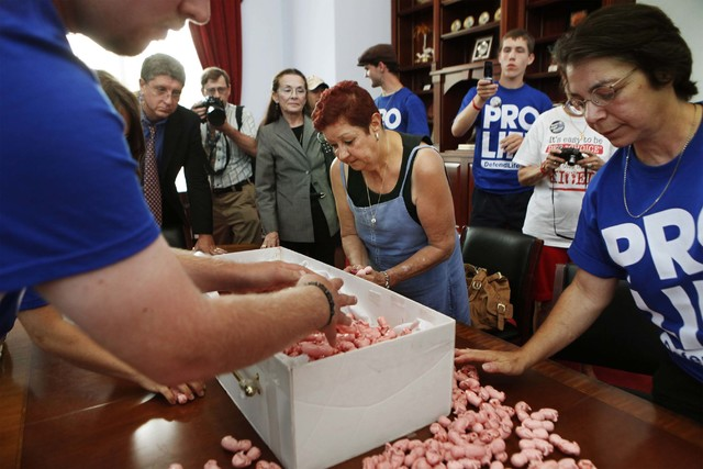Norma McCorvey, center, the plaintiff in the landmark lawsuit Roe v. Wade, and Monica Migliorino Miller, right, help gather plastics in the shape of babies, each symbolizing babies, during a anti- ...