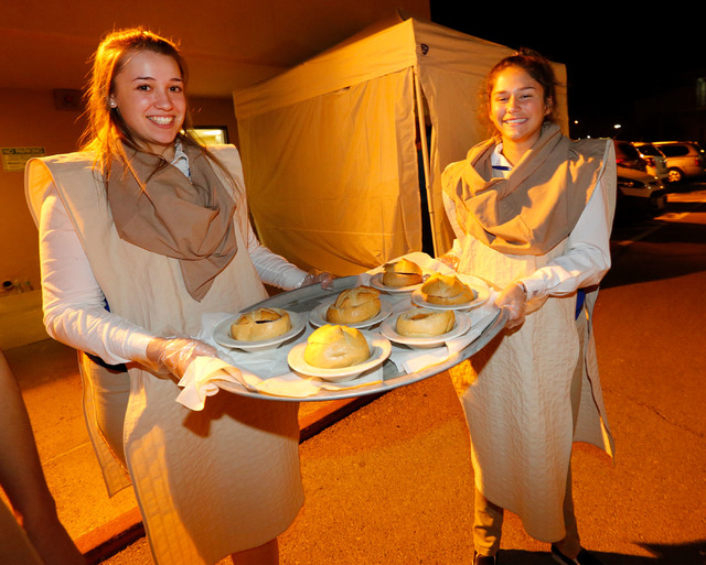 Bishop Gorman High School students Kayla Unkelbach, 16, and Olivia Stabile, 15, carries a plate during a medieval feast at UNLV Catholic Newman Center in Las Vegas, Sunday, Jan. 29, 2017. (Chitose ...