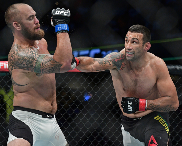 Fabricio Werdum, right, from Brazil, punches Travis Browne during a heavyweight bout at UFC 203 on Saturday, Sept. 10, 2016, in Cleveland. (AP Photo/David Dermer)