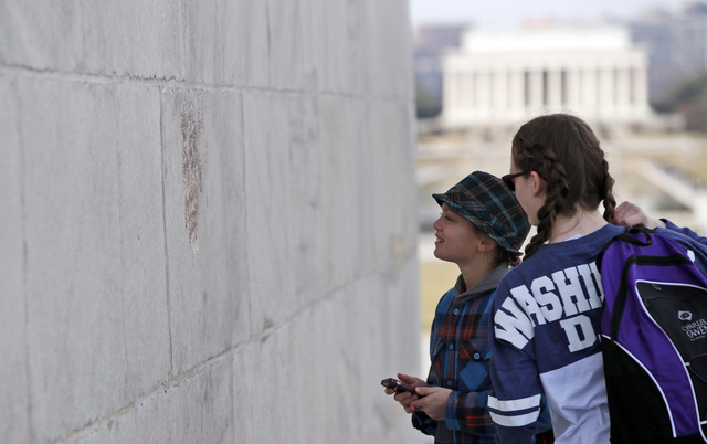 With the Lincoln Memorial in the background, people look at graffiti on the Washington Monument, Tuesday, Feb. 21, 2017, in Washington. Messages written in permanent marker were discovered over th ...