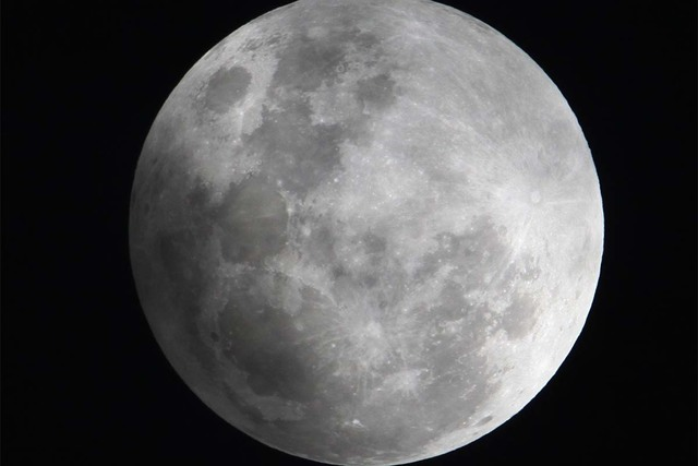 In this Monday Feb. 9, 2009 file photo, a faint shadow from the earth is cast over part of the moon during a penumbra lunar eclipse, seen from Manila, Philippines. Friday, a partial eclipse and Co ...