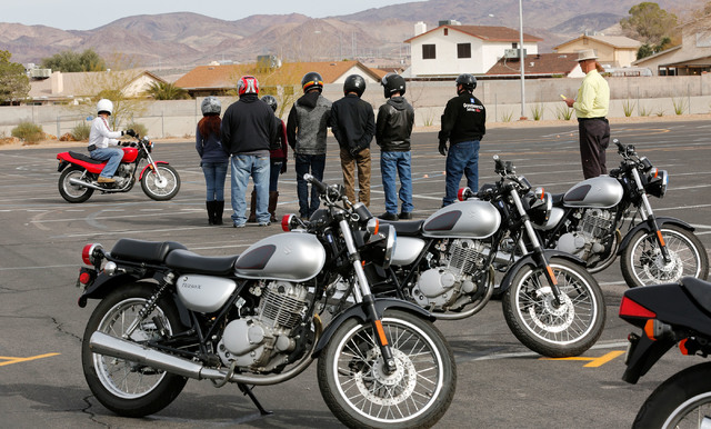 """Instructor Patrick Soles, left, demonstrates during a College of Southern Nevada motorcycle safety course as participants and another instructor, Mike """"Pilot"""" Nelson, right, look on at the college ..."""