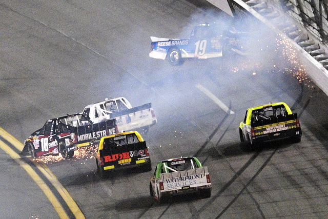 Austin Cindric (19) hits the wall as Noah Gragson (18) and Ryan Truex (16) collide in a multi-vehicle crash in Turn 1 during the NASCAR Trucks auto race at Daytona International Speedway, Friday,  ...