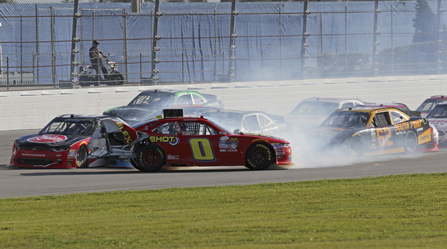 Garrett Smithley (0) crashes in front of several cars including Brendan Gaughan (62) during a NASCAR Xfinity series auto race at Daytona International Speedway in Daytona Beach, Fla., Saturday, Fe ...