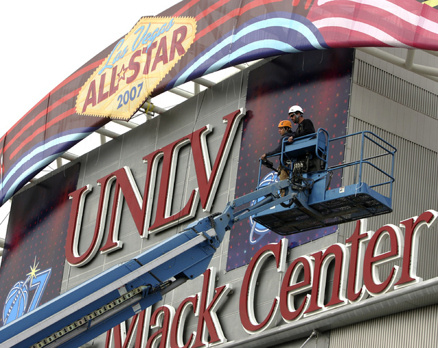 Workers finish installing banners at the Thomas and Mack Center in preparation for the NBA All-Star game this weekend. (John Gurzinski/Las Vegas Review-Journal)