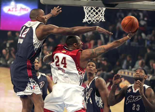 NBA Eastern Conference player (L) Dwight Howard tries to block NBA Western Conference player (R)  Kobe Bryant as he tries to score during the All-Star basketball game at the Thomas and Mack Center ...