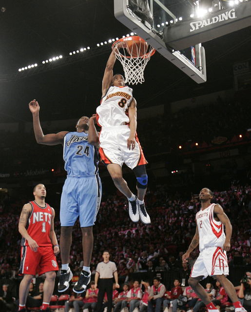 Monta Ellis of the Sophomore team makes a dunk over Paul Millsap of the Rookie team in the NBA All-Star Rookie Challenge basketball game at the Thomas & Mack Center in Las Vegas Saturday, Feb. ...