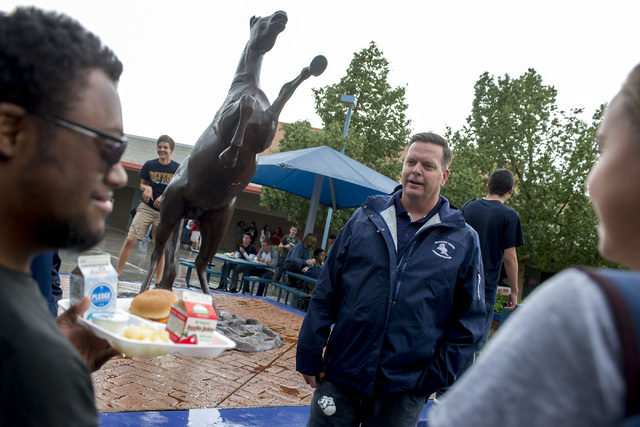 Principal Travis Warnick talks with students during their lunch about the new mascot statue, pictured in background, that arrived that day at Shadow Ridge High School in Las Vegas. Warnick was nam ...