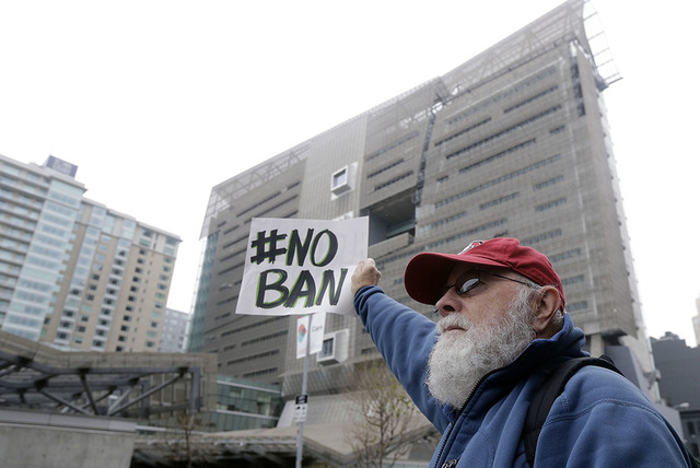 David Pearce holds a sign outside of the 9th U.S. Circuit Court of Appeals in San Francisco, Tuesday, Feb. 7, 2017. (AP Photo/Jeff Chiu)