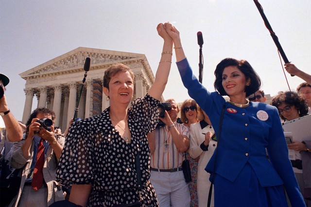 Norma McCorvey, Jane Roe in the 1973 court case, left, and her attorney Gloria Allred hold hands as they leave the Supreme Court building on Wednesday, April 26, 1989, in Washington after sitting  ...