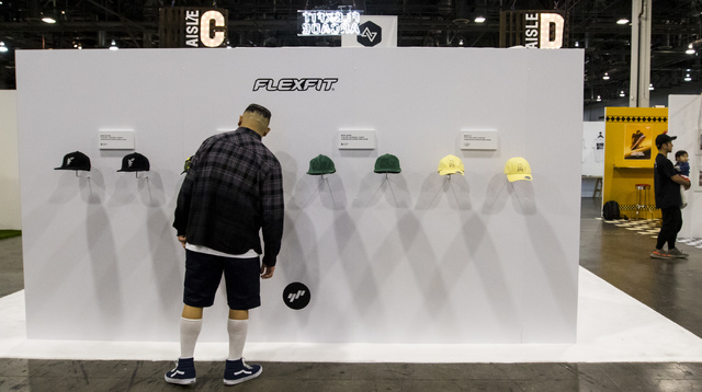 An attendee looks at a wall of FlexFit hats at the Off Price Expo at the Sands Expo and Convention Center in Las Vegas on Monday, Feb. 20, 2017. (Miranda Alam/Las Vegas Review-Journal) @miranda_alam