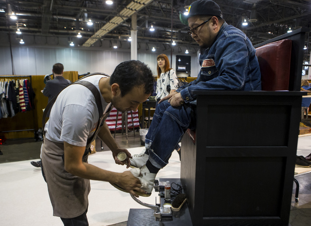 Takeshi Inoue of Japan gets his boots shined by Salvador Castillo in front of the Red Wing Shoes booth at the Off Price Expo at the Sands Expo and Convention Center in Las Vegas on Monday, Feb. 20 ...