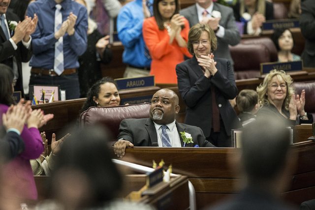 Assembly Speaker Jason Frierson, middle, holds back tears as he's given a round of applause after being sworn in during the first day of the Nevada Legislative session on Monday, Feb. 6, 2017, at  ...