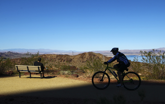 Kurt Zingelman, left, of Boulder City takes in a view of the lake as a cyclist passes by on the Historic Railroad Trail at Lake Mead National Recreation Area on Tuesday, Feb. 14, 2017. (Chase Stev ...